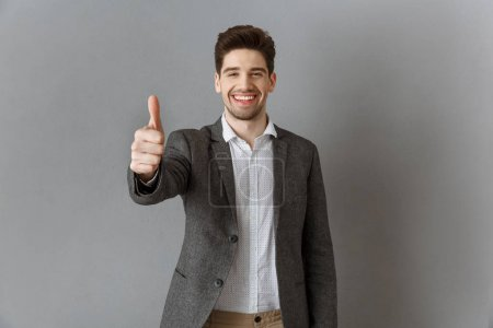 portrait of smiling businessman in suit showing thumb up against grey wall