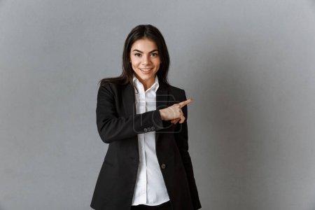Foto de Retrato de empresaria sonriente en juego apuntando a telón de fondo gris de la pared - Imagen libre de derechos
