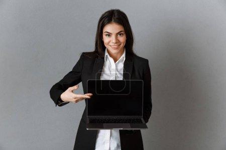 Foto de Retrato de empresaria sonriente señalando portátil con pantalla en blanco sobre fondo gris de la pared - Imagen libre de derechos