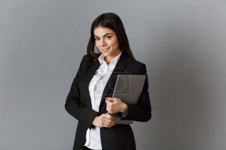 Photo for Portrait of smiling businesswoman with laptop against grey wall background - Royalty Free Image
