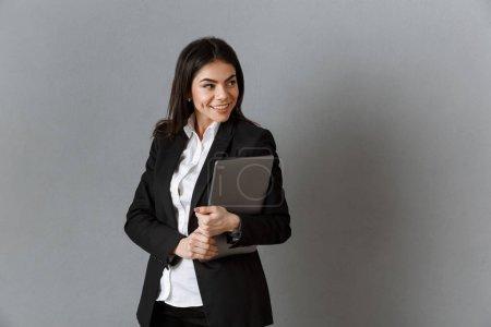 retrato de mujer de negocios sonriente con portátil contra fondo de pared gris