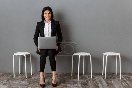 Photo pour Sourire de femme d'affaires en costume avec ordinateur portable en attente pour l'entrevue d'emploi - image libre de droit