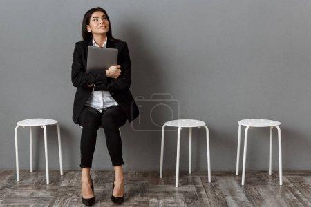 Photo pour Femme d'affaires songeur en costume avec ordinateur portable en attente pour l'entrevue d'emploi - image libre de droit