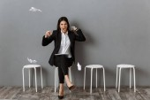 angry and stressed businesswoman in suit with wrapped papers waiting for job interview