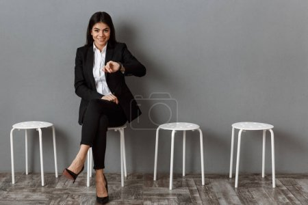 Photo for Smiling businesswoman in suit waiting for job interview - Royalty Free Image