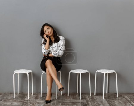 asian businesswoman talking on smartphone while waiting for job interview