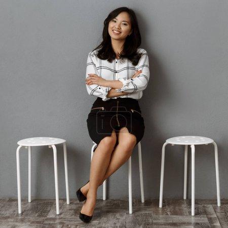 Photo pour Souriante femme asiatique avec les bras croisés d'attente pour l'entrevue d'emploi - image libre de droit