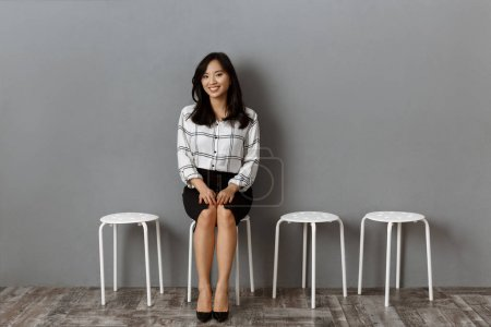 Photo for Smiling asian businesswoman sitting on chair while waiting for job interview - Royalty Free Image