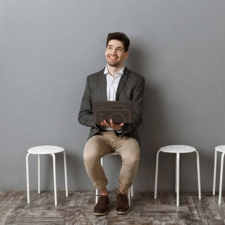 Photo for Smiling businessman with laptop waiting for job interview - Royalty Free Image