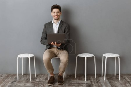 smiling businessman with laptop looking at camera while waiting for job interview