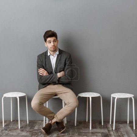 pensive businessman waiting for job interview on chair against grey wall