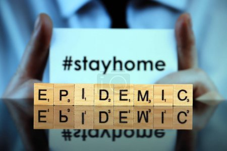 Photo for WROCLAW, POLAND - MARCH 30, 2020: The word EPIDEMIC made of wooden letters, and man holding a business card with the words STAY HOME (with hashtag, popular on social media) in the background. - Royalty Free Image