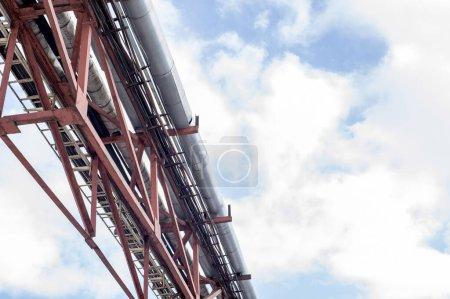 Photo pour Métallurgie de la ferme du pipeline à travers l'air contre le ciel. Le système d'alimentation en eau, chauffage, environnement pneumomandrel et électricité. Contexte industriel . - image libre de droit