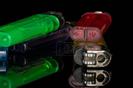 Photo pour Groupe de quatre briquets en plastique clair isolés sur verre noir - image libre de droit