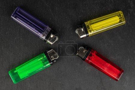 Photo pour Groupe de quatre allume-feu en plastique sur pierre grise - image libre de droit