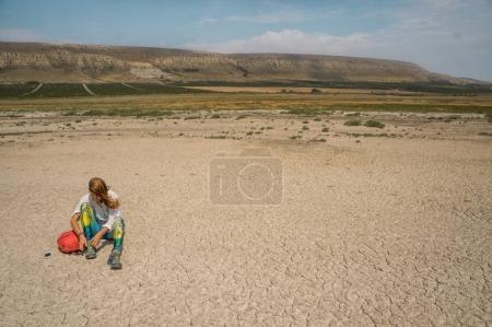 girl sitting on cracked earth