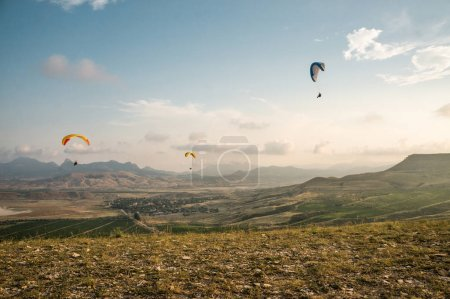 People flying on paragliders
