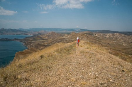 woman in mountains with sea