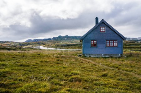 Foto de Beautiful landscape with little house on meadow with mountains and river, Norway, Hardangervidda National Park, september 2015 - Imagen libre de derechos