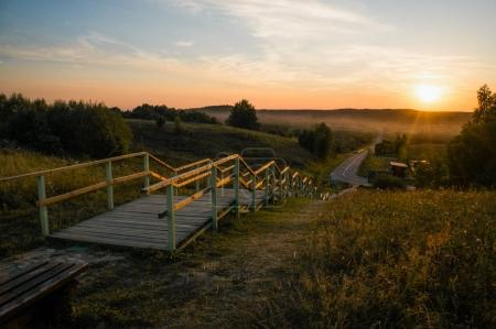 Photo pour Wooden stairs to the road at beautiful sunset, Belarus, Braslav - image libre de droit
