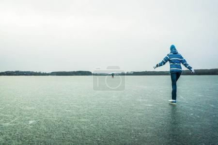 Photo for Back view of people in winter clothing skating on ice, Belarus, Sosnovka - Royalty Free Image