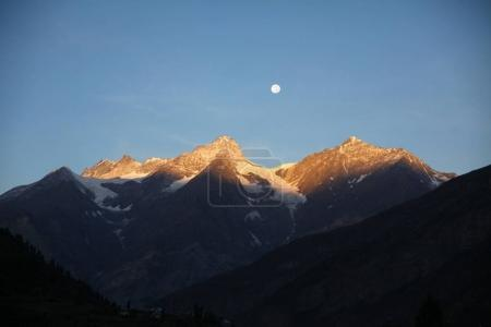 Photo for Beautiful scenic landscape with snow capped mountains and moon in indian himalayas - Royalty Free Image