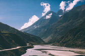 scenic landscape with river in majestic valley and road with vehicles in indian himalayas