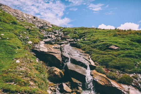 Photo for Beautiful small waterfall on rocks and green grass in Indian Himalayas, Rohtang Pass - Royalty Free Image