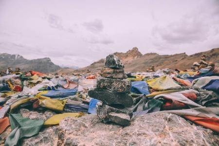 pile of stones and colorful prayer flags on mountain peak in Indian Himalayas, Ladakh region