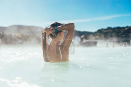 rear view of young woman relaxing in hot pool in Iceland