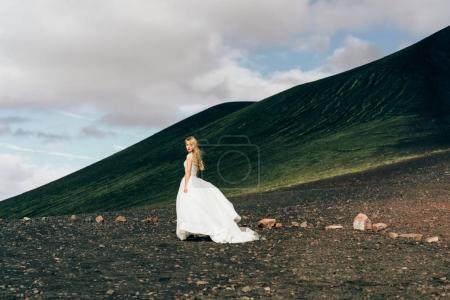 Photo for Beautiful young bride in white wedding dress walking at amazing icelandic nature - Royalty Free Image