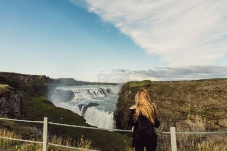 Photo for Back view of young woman looking at scenic majestic waterfall in Iceland - Royalty Free Image