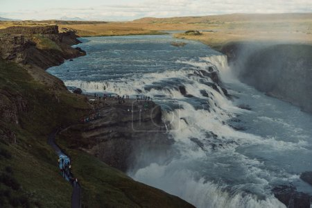 Photo for Group of tourists looking at majestic waterfall in Iceland - Royalty Free Image