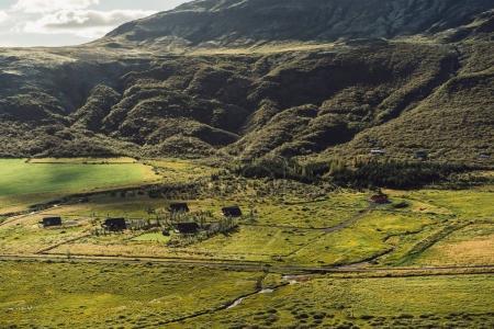 Photo pour Beau paysage avec des collines herbeuses et des maisons en Islande - image libre de droit