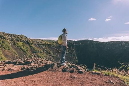 Photo for Side view of young bearded man with backpack looking at scenic crater lake in Iceland - Royalty Free Image