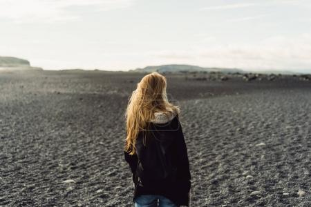 Photo for Back view of young woman looking at beautiful wild icelandic landscape - Royalty Free Image