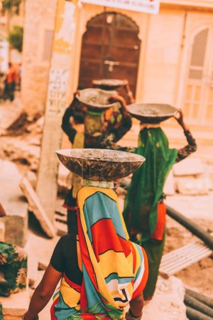 back view of women in bright traditional clothes carrying bowls on heads, rajastan, jeisalmir