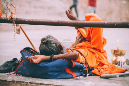 monk in bright orange clothing resting in Varanasi, India