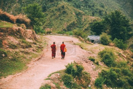 back view of two monks walking on mountain road in Indian Himalayas, Dharamsala, Baksu