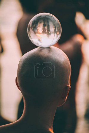 close-up back view of young man standing with glass ball on head, Goa