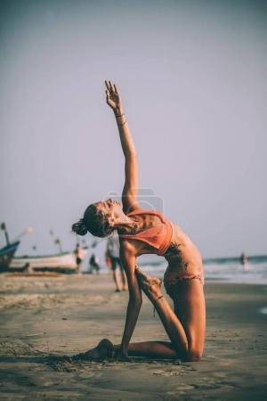 Photo for Young flexible woman in swimsuit practicing yoga on sandy beach at goa - Royalty Free Image