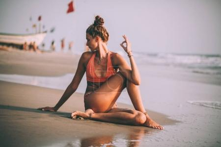 young woman in swimsuit practicing yoga on beach at goa