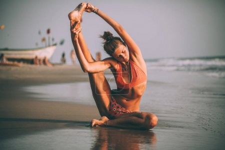 Photo for Young flexible woman in swimsuit practicing yoga on beach at goa - Royalty Free Image