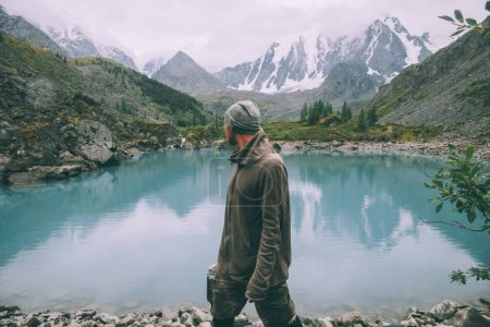 Photo for Side view of man looking at majestic calm mountain lake in Altai, Russia - Royalty Free Image