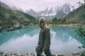 side view of man looking at majestic calm mountain lake in Altai, Russia