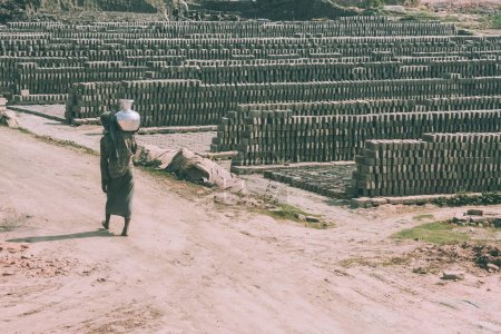 Photo for Poor barefoot person carrying pitcher on shoulder and outdoor warehouse of bricks around in Nepal - Royalty Free Image