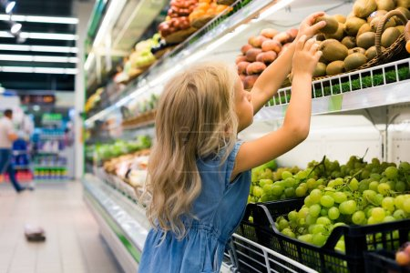 adorable female child choosing fruits in supermarket