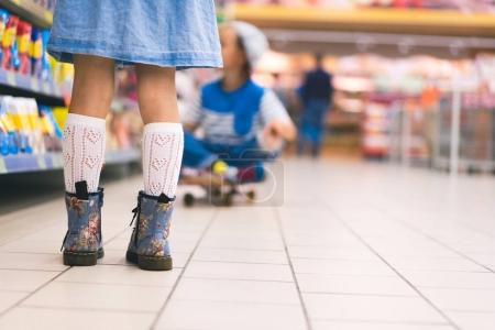 cropped view of female kid standing in supermarket