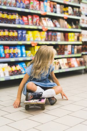 blonde kid sitting on skateboard in supermarket with shelves behind