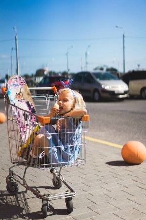 little female child eating chips while sitting in shopping cart with skateboard